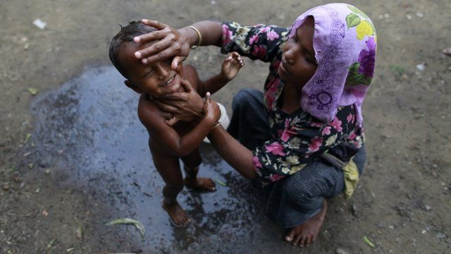 A woman, from Rohingya internally displaced persons (IDP) camp, bathes her son in a school where she and others were evacuated to shelter from cyclone Mahasen when it landed,