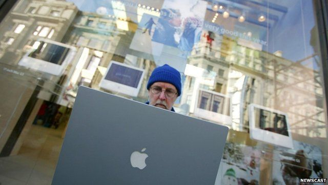 Customer logs onto a laptop whilst waiting for the new Apple store in London to open