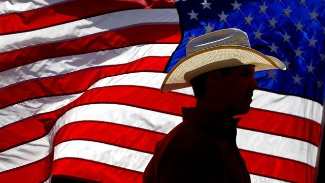 A cowboy hat silhouetted against the US flag