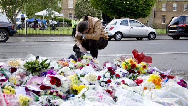 A man pays his respects as he looks at floral tributes outside Woolwich Barracks in London