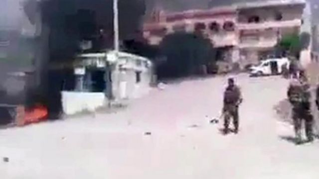 Still from video showing fighter in square, fires burning