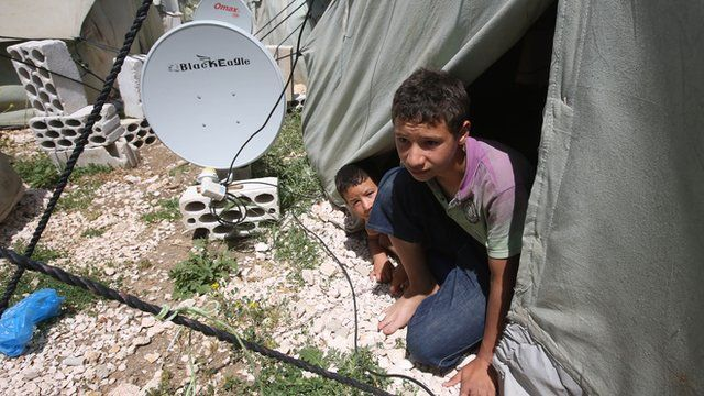 Syrian refugees sitting in their tent in a refugee camp in Lebanon.