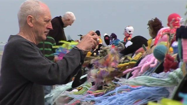 Man taking pictures of knitted figures in Saltburn