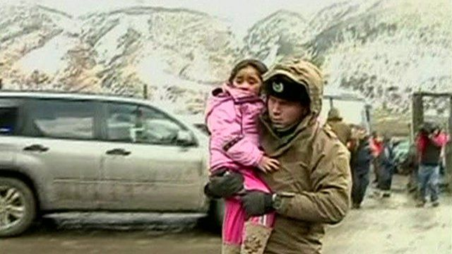 A soldier carries a girl to a truck
