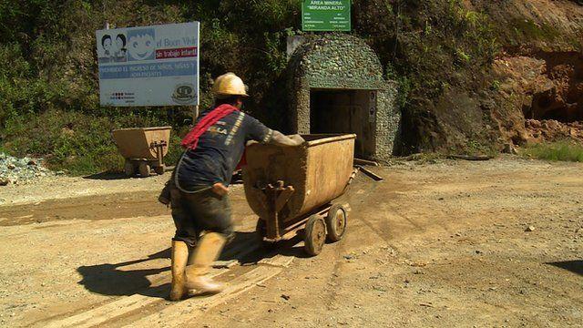 Man pushing cart outside gold mine in Ecuador