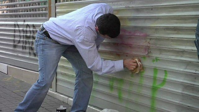Man scrubs graffiti from street in Istanbul