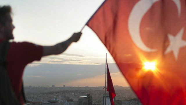 A protestor waves the Turkish flag from a roof top at Taksim square on June 3, 2013 in Istanbul, Turkey