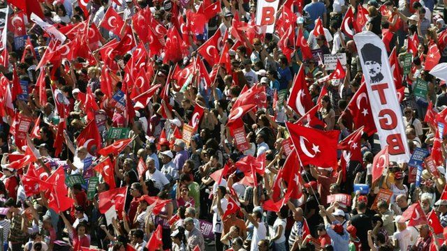 Anti-government protesters wave flags during a rally in Istanbul's Taksim square