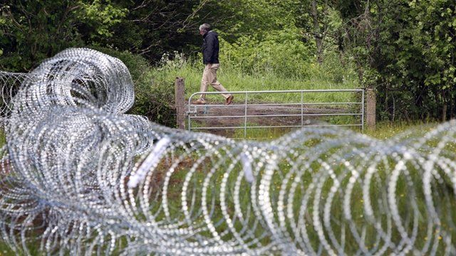 A man walks past razor wire which has been laid in fields near the Lough Erne resort in County Fermanagh