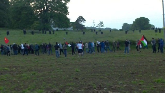 Protesters inside the cordon and riot police scattered on the hill