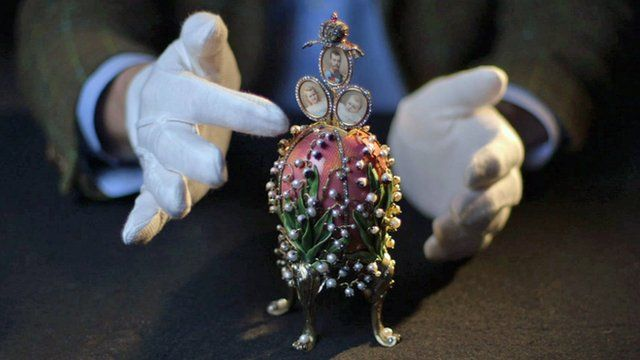 Gloved hands and a Faberge egg