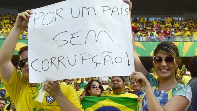 """Brazilian football fans show a poster reading """"For a Country Without Corruption"""""""