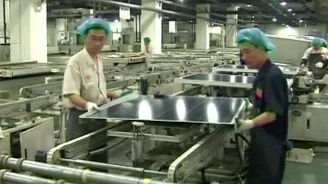 Chinese factory workers handling a solar panel
