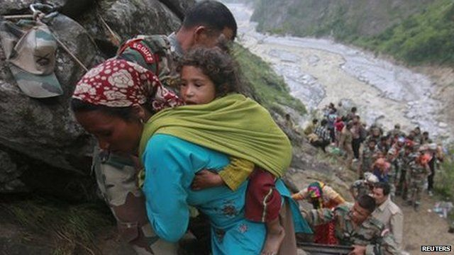 Soldiers assist a woman carrying a child on her back during rescue operations in Govindghat in Uttarakhand on June 23, 2013