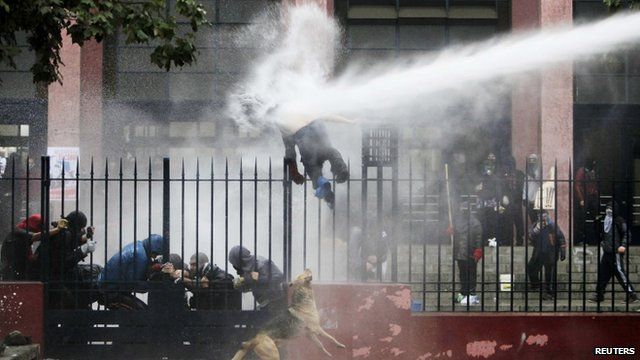 A student is hit by a jet of water sprayed by riot police in Santiago