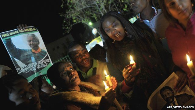 Well-wishers hold candles and photos of Nelson Mandela outside the Mediclinic heart hospital in Pretoria