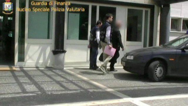 Nunzio Scarano leaving building accompanied by policemen