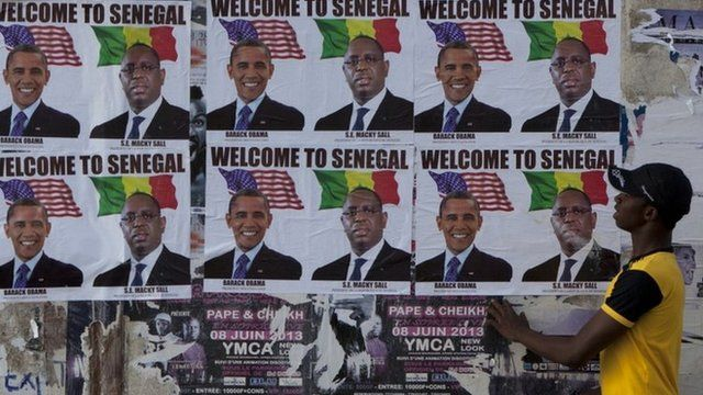 "A passerby stops to look at signs showing US President Barack Obama alongside Senegalese President Macky Sall and reading ""Welcome to Senegal"" in Dakar, Senegal, Wednesday 26 June 2013"