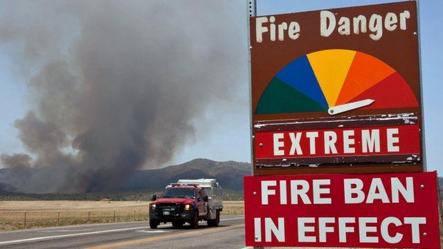 A fire engine passes by a fire ban sign as the Yarnell Hill Fire advances on Peeples Valley, Arizona