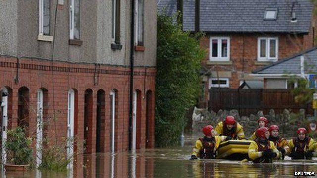 Firefighters pull a boat as they wade down a flooded street in St Asaph