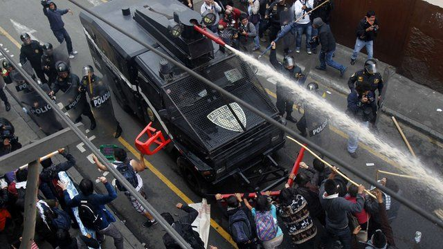 Students try to push a police truck as they clash with riot police in Lima
