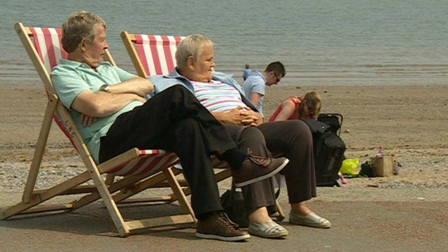 People on deckchairs on a beach