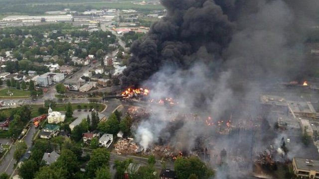 Smoke rises from railway cars that were carrying crude oil after derailing in downtown Lac Megantic