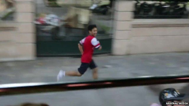 Vu Xuan Tien running alongside the Arsenal bus