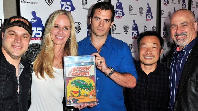 DC Comics figures with Henry Cavill, holding the first issue of Action Comics, in which Superman debuted