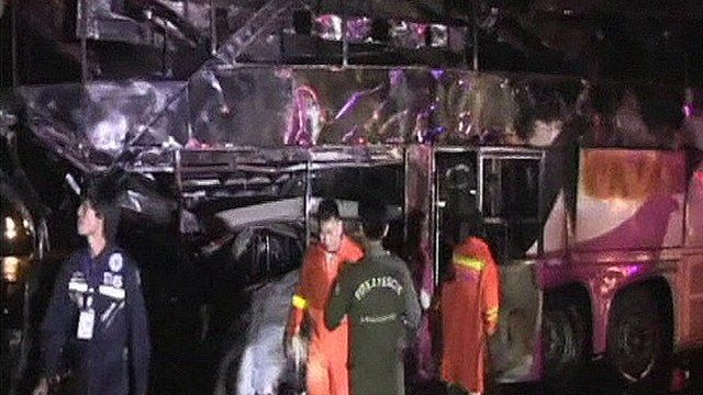 Rescue workers in front of the burnt-out bus