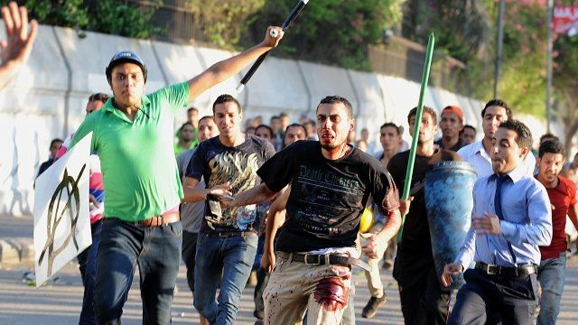 A supporter of ousted President Mohammed Morsi (centre) runs from pro-government and army supporters
