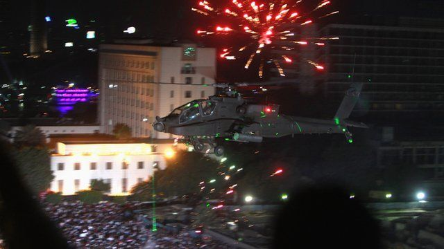 An Apache helicopter flies over Tahrir Square as a firework explodes