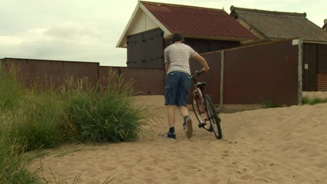 Man pushing bicycle on sand
