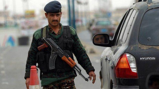 A Yemeni soldier checks vehicles