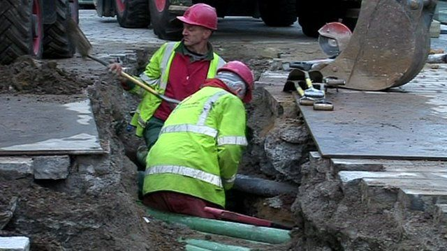 Workmen digging around pipes
