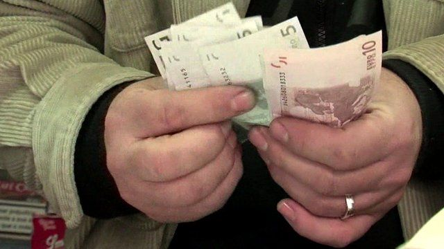 Shopkeeper counting euro notes