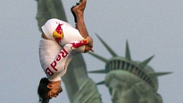 Orlando Duque performs a 75-foot tuck dive from a helicopter, beside the Statue of Liberty in New York.