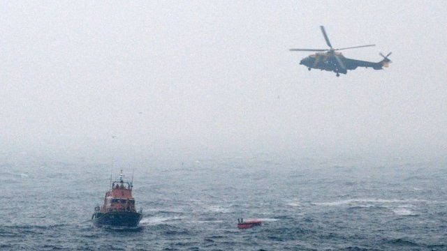 Rescue helicopter and lifeboat reaching a life raft