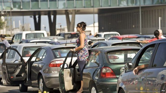 Woman standing by car in middle of traffic