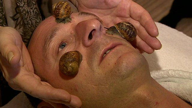 A man has three snails placed on his face