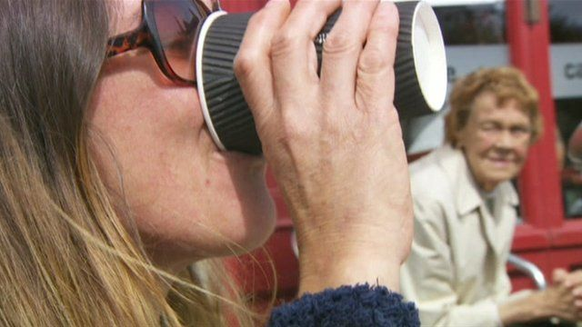 Woman drinking from paper cup