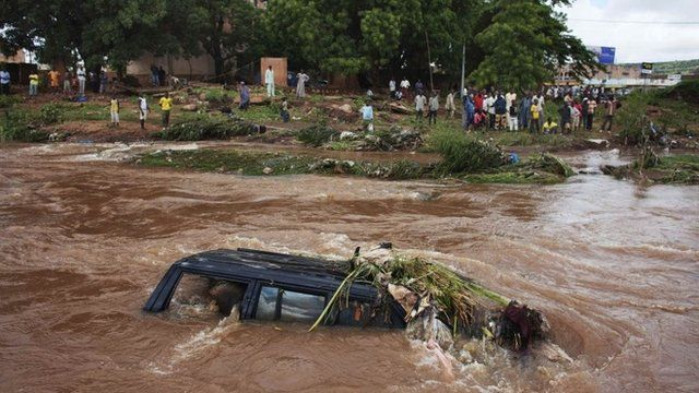 People look at a SUV submerged in floodwaters in Bamako