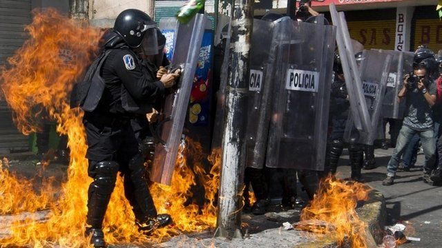 Mexican police stand amid flames from an incendiary device during protests in Mexico City