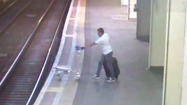 CCTV of man pushing trolley onto train tracks