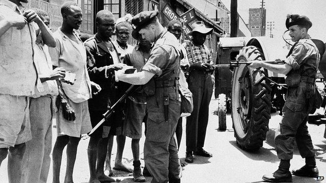 British soldiers check the identity of men during a raid on parts of Kenya in 1953, looking for Mau Mau members.