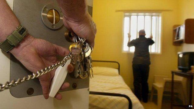 A prison warder locks a prisoner in a prison cell