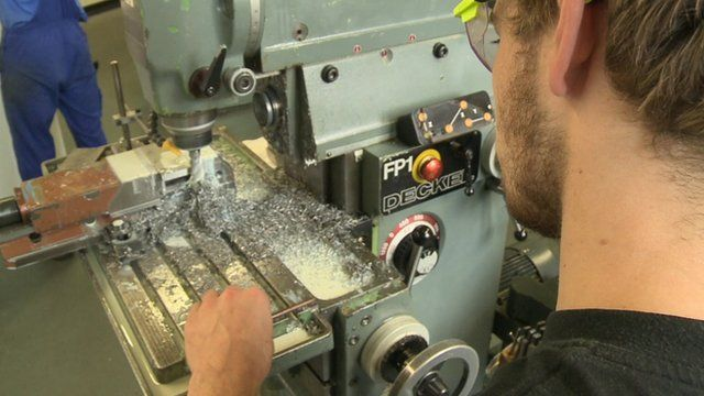 A young man using an industrial drill