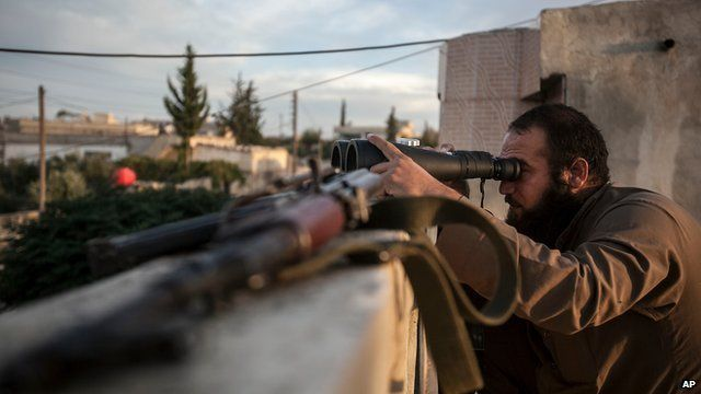 A Syrian opposition fighter watches over as heavy fighting sparks out in the neighbouring village of Kafr Nabuda