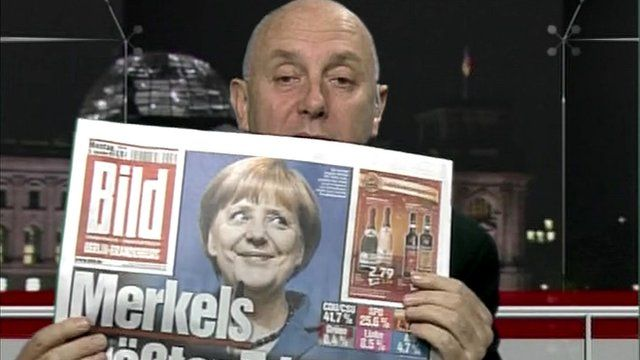 Steve Evans holds German newspaper