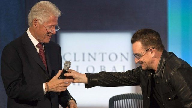 The lead singer of Irish rock group U2, Bono (R), bows as he hands the microphone to former U.S. President Bill Clinton after Bono had been imitating him on stage at the Clinton Global Initiative 2013